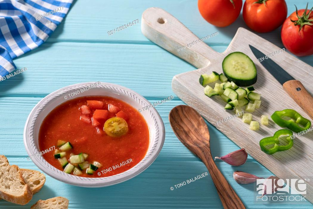 Stock Photo: Gazpacho Andaluz is an Andalusian tomato cold soup from Spain with cucumber, garlic, pepper on light blue background.