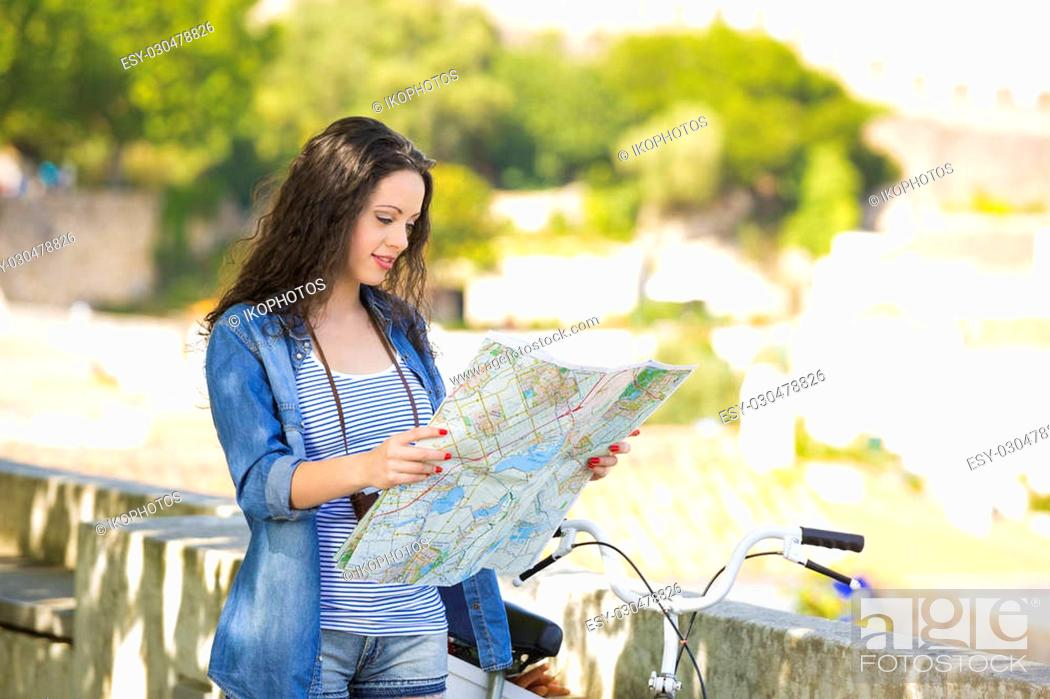 Stock Photo: A young and beautiful female tourist searching a place on the map.