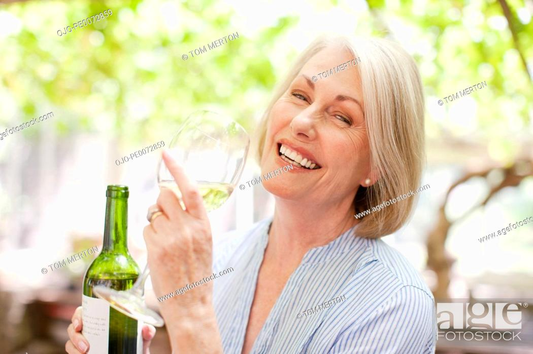 Stock Photo: Smiling woman drinking white wine.