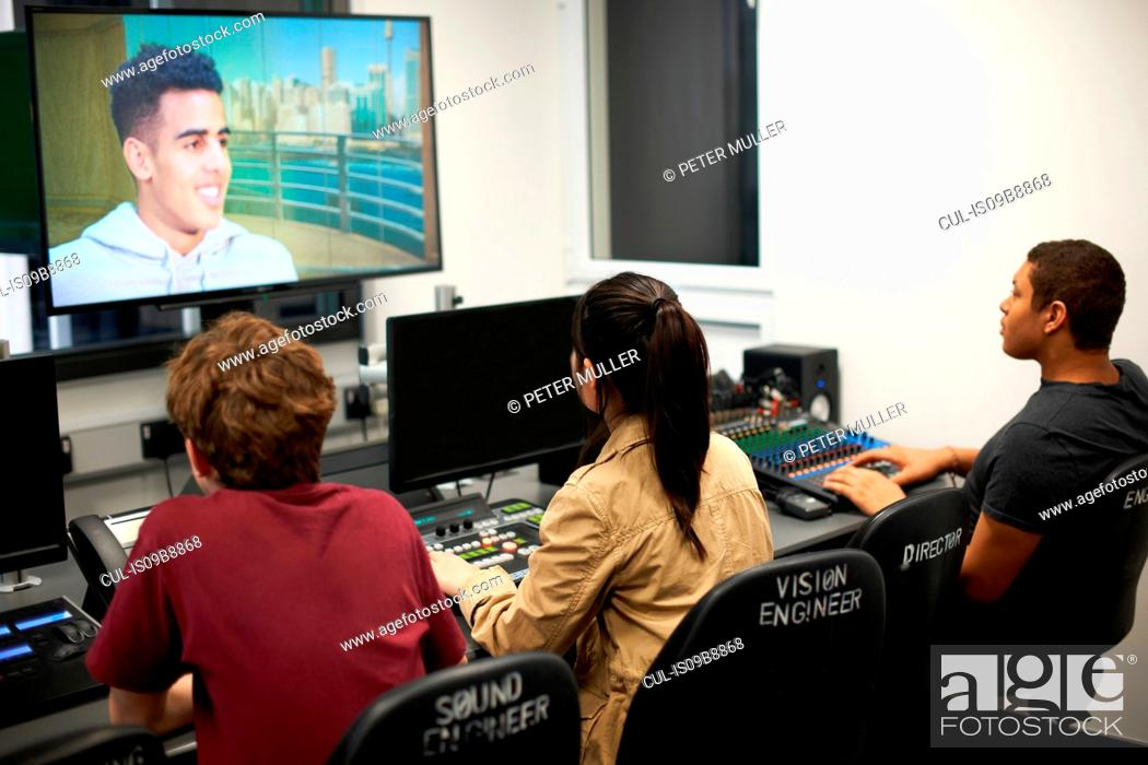 Stock Photo: Young male and female college students at mixing desk watching TV screen.