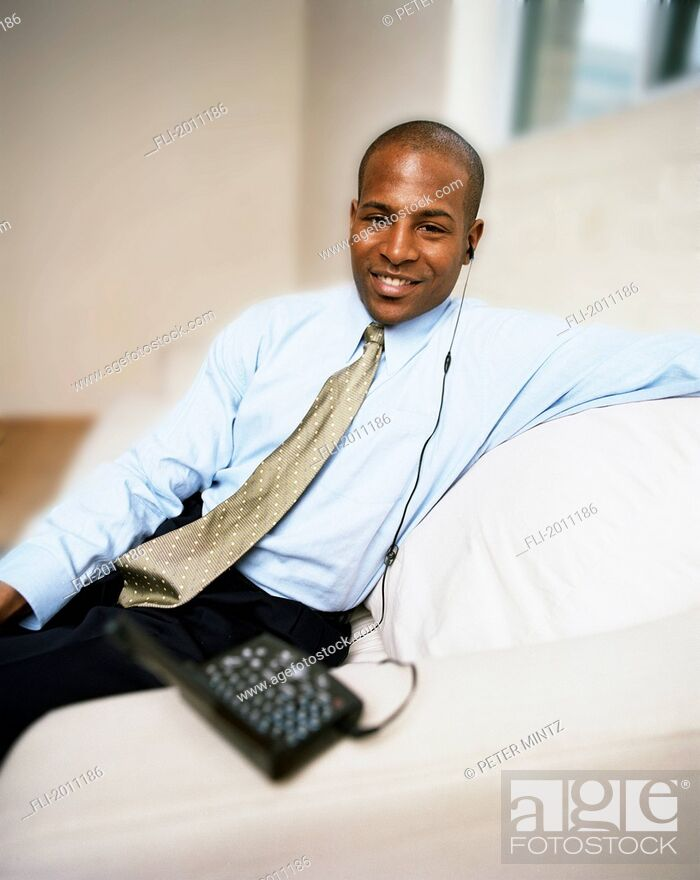 Stock Photo: Fv3201, Peter Mintz; Businessman On Couch With Blackberry, Mobile Wireless Internet Device, Using Earphone.