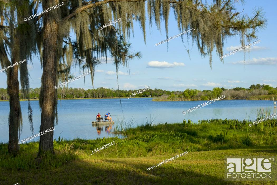 Stock Photo: Husband and wife fishing from a small boat together for bass fish on Hardee Lake County Park Florida campground.