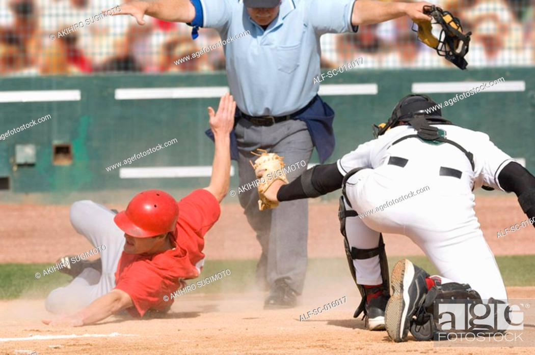 Stock Photo: Baseball player sliding into home plate.