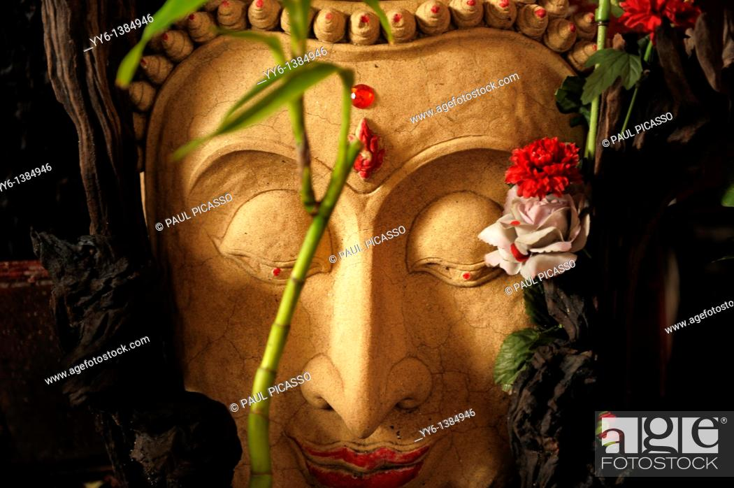 Stock Photo: buddha stone image decorated with flowers , chinatown , bangkok, thailand.