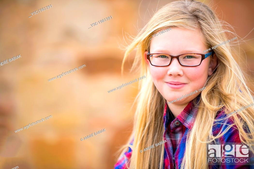 Stock Photo: USA, Texas, Portrait of girl (12-13) with long blond hair and glasses.