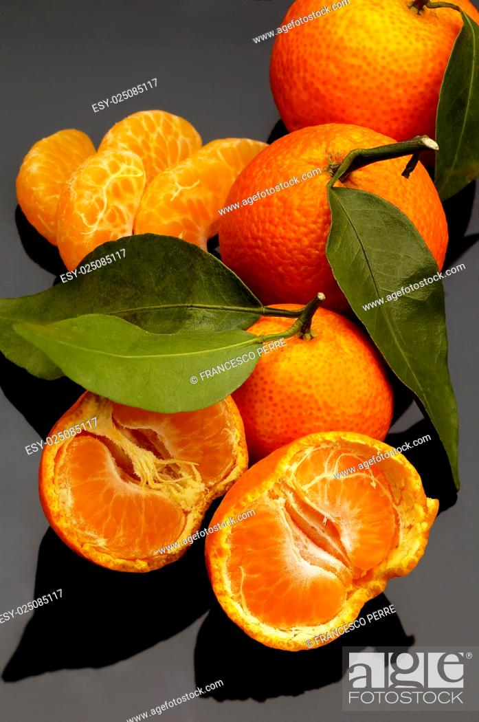 Stock Photo: vivid orange tangerine on black reflective surface.