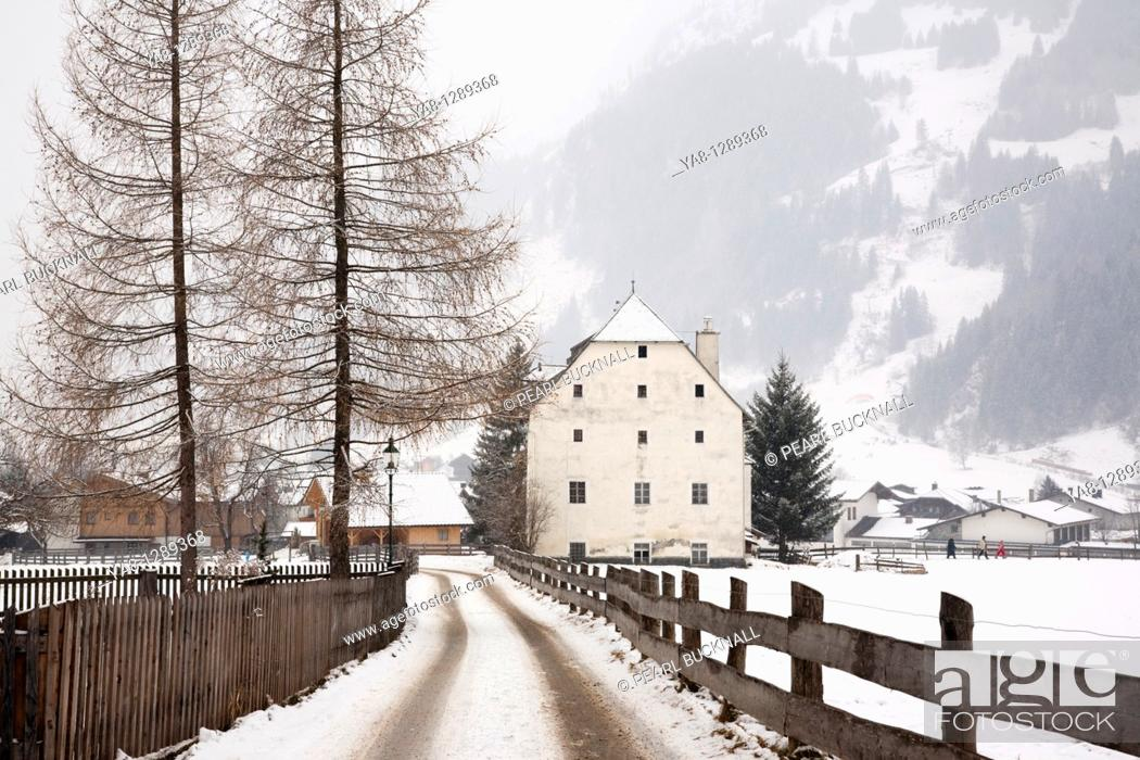 Stock Photo: Rauris Austria Europe  Winter snow scene and lane to 16th century historic building Furstenmuhle former bakery and mill 1565 in Alpine village.