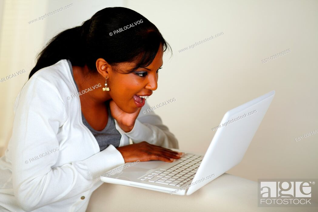 Stock Photo: Portrait of a surprised young woman reading a message on laptop screen.