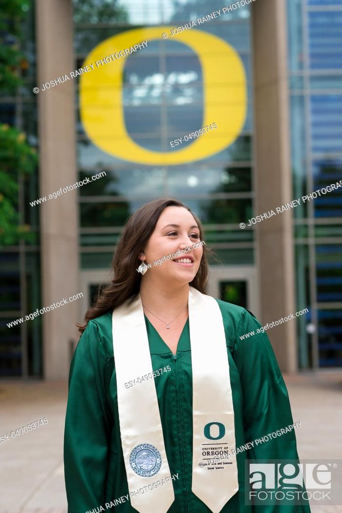 Stock Photo: Eugene, OR - May 19, 2019: University of Oregon graduate Lacie Brown celebrates her graduation in cap and gown on campus in Eugene.