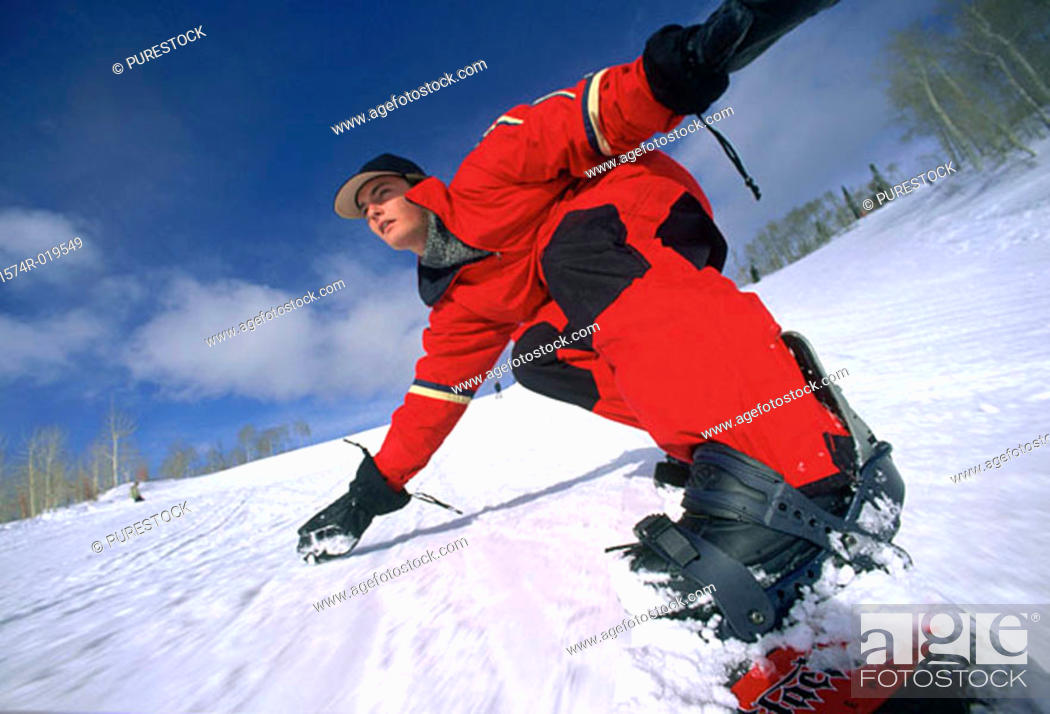 Stock Photo: Young adult man snowboarding downhill.