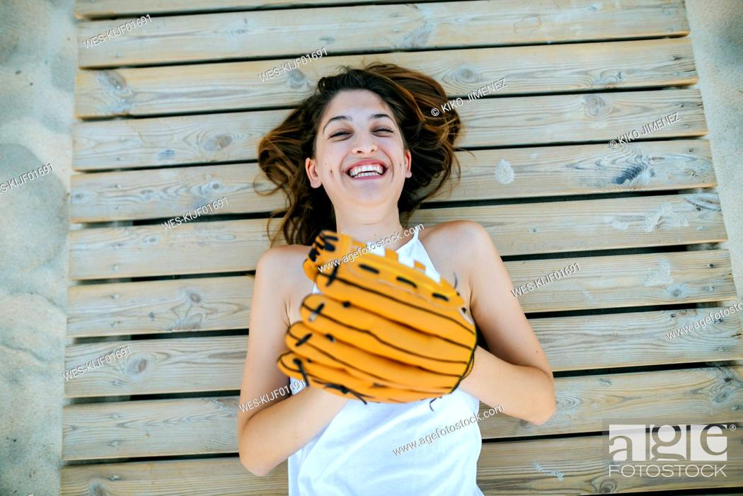Stock Photo: Young woman lying on wooden path laughing with baseball glove.