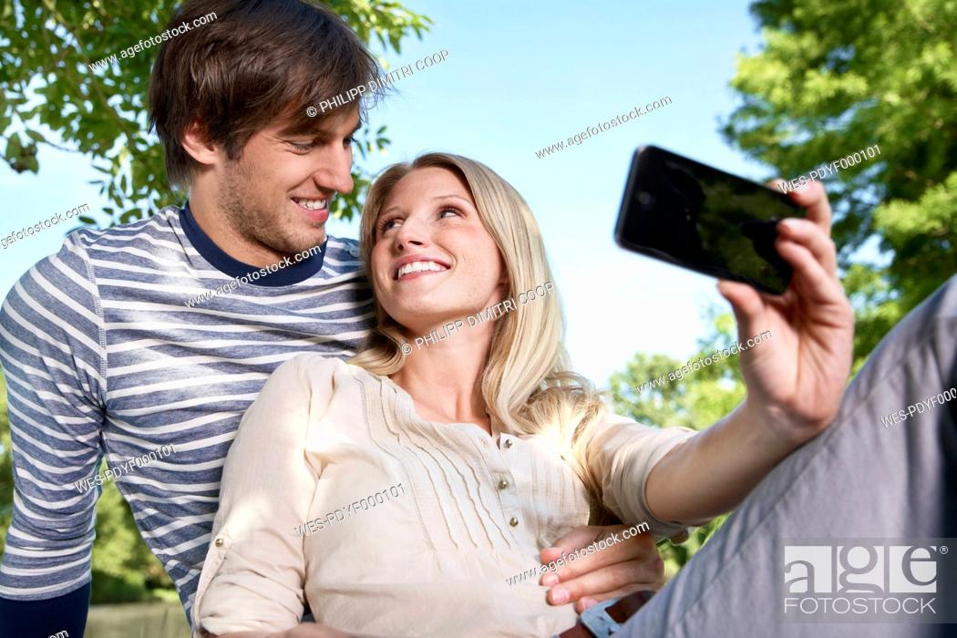 Stock Photo: Germany, Cologne, Young couple taking self photograph, smiling.