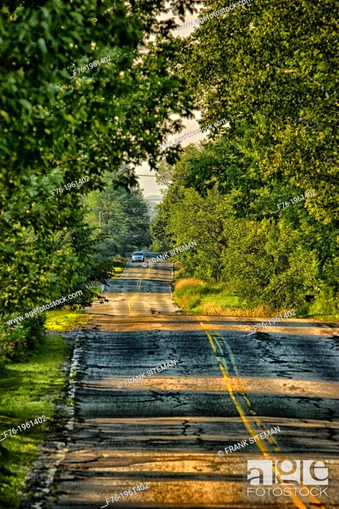 Stock Photo: Rural road in Lancaster, NH with car with headlights on approaching, USA.