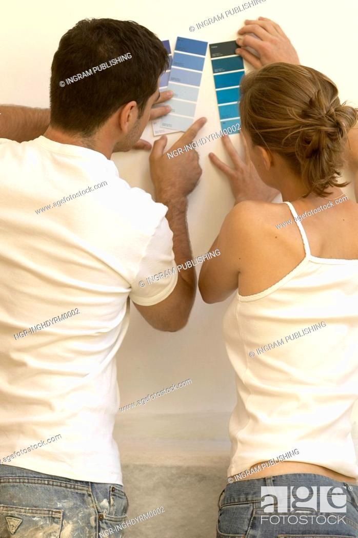 Stock Photo: Rear view of a young couple holding paint shade cards on a wall.