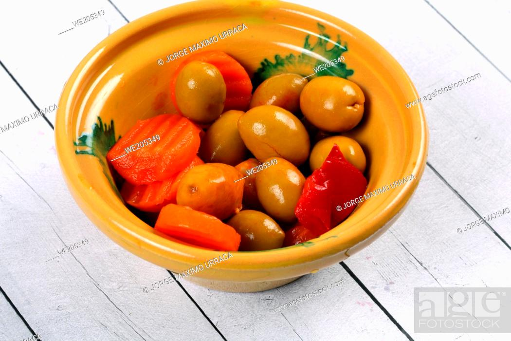 Stock Photo: Olives in a ceramic bowl on a white wooden board.
