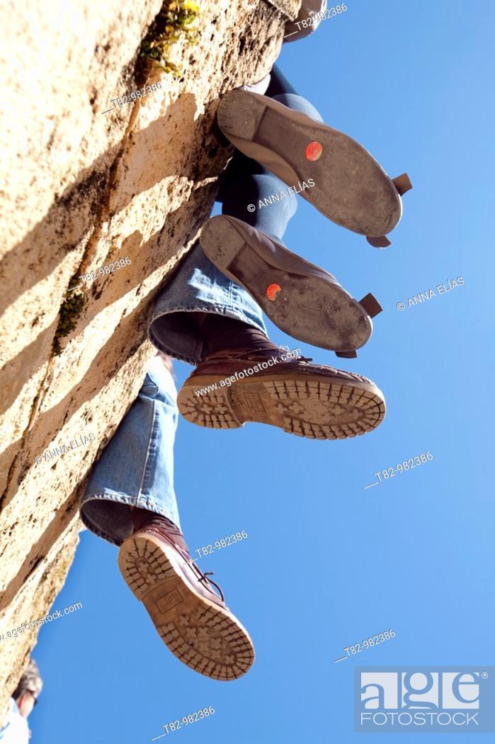 Stock Photo: contrapicado de dos pies de mujer y dos pies de hombre sentados en una pared sobre cielo azul en Sevilla,Contrapicado woman two feet and two feet of a man.