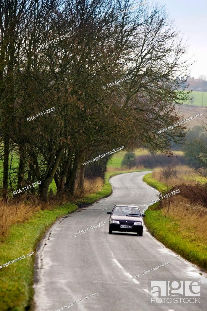 Stock Photo: Car driving on a country road near Burford in the Cotswolds, Oxfordshire, United Kingdom.