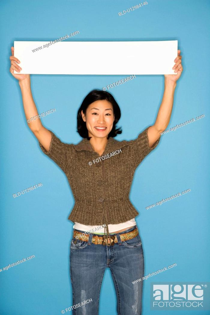 Stock Photo: Woman holding blank sign on blue background.