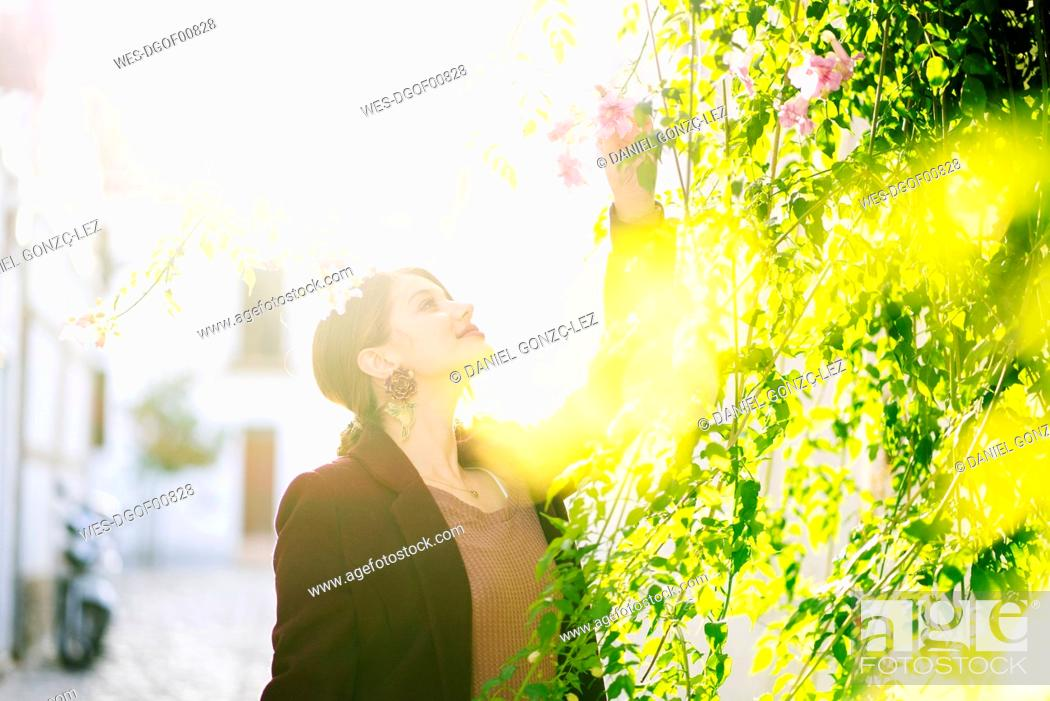 Stock Photo: Smiling woman with a blossom in a scenic alley in the city.