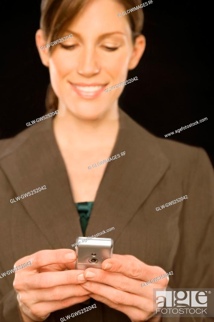 Stock Photo: Close-up of a businesswoman text messaging.