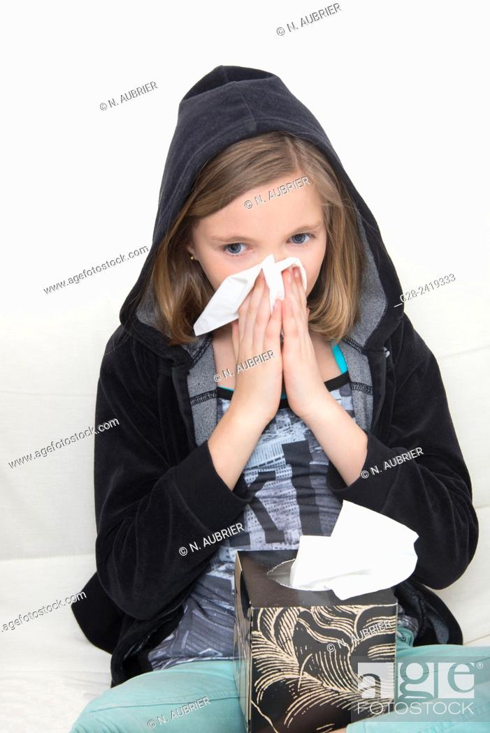 Stock Photo: girl in a black hood, blowing her nose and sneezing.
