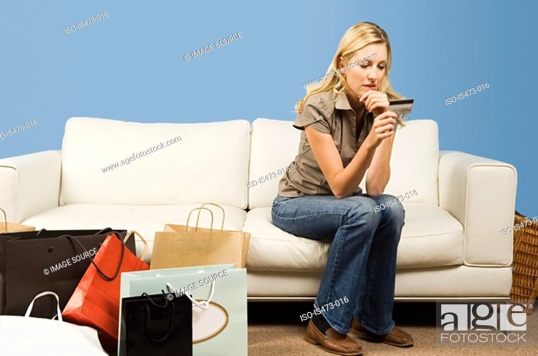 Stock Photo: Woman looking at credit card.