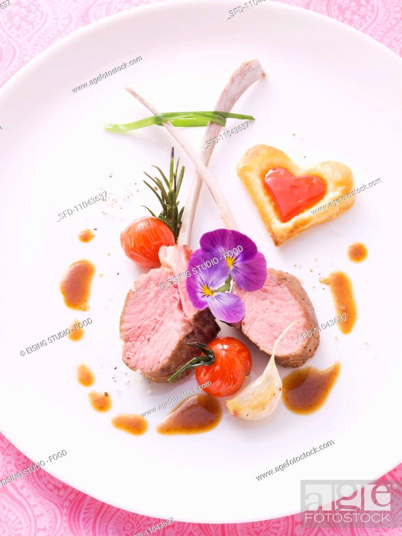 Stock Photo: Medium rare lamb chops with heart-shaped puff pastries.