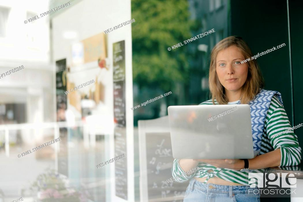 Imagen: Portrait of young woman with laptop in a cafe.