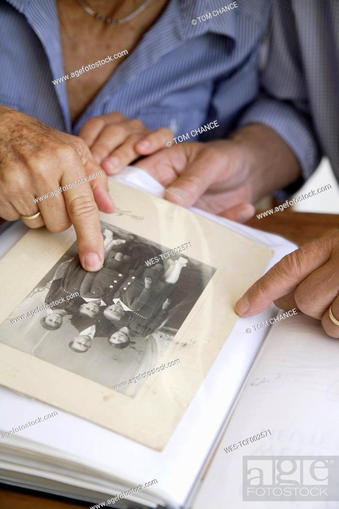 Stock Photo: Germany, Bavaria, Senior couple with photo album.