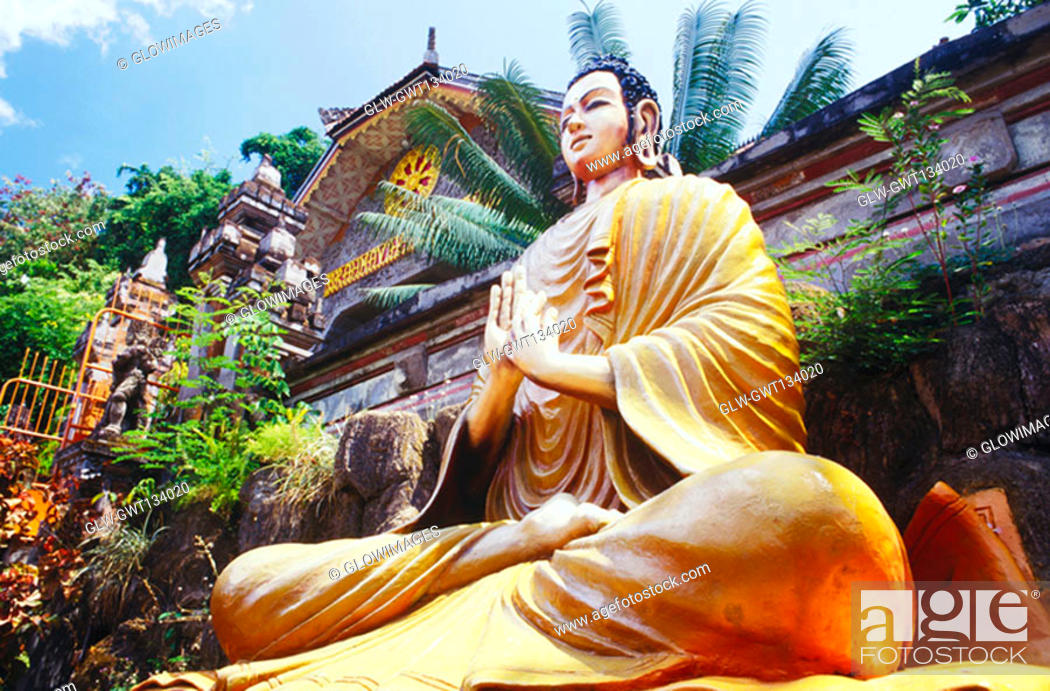 Stock Photo: Low angle view of a statue of Buddha in front of a building, Bali, Indonesia.