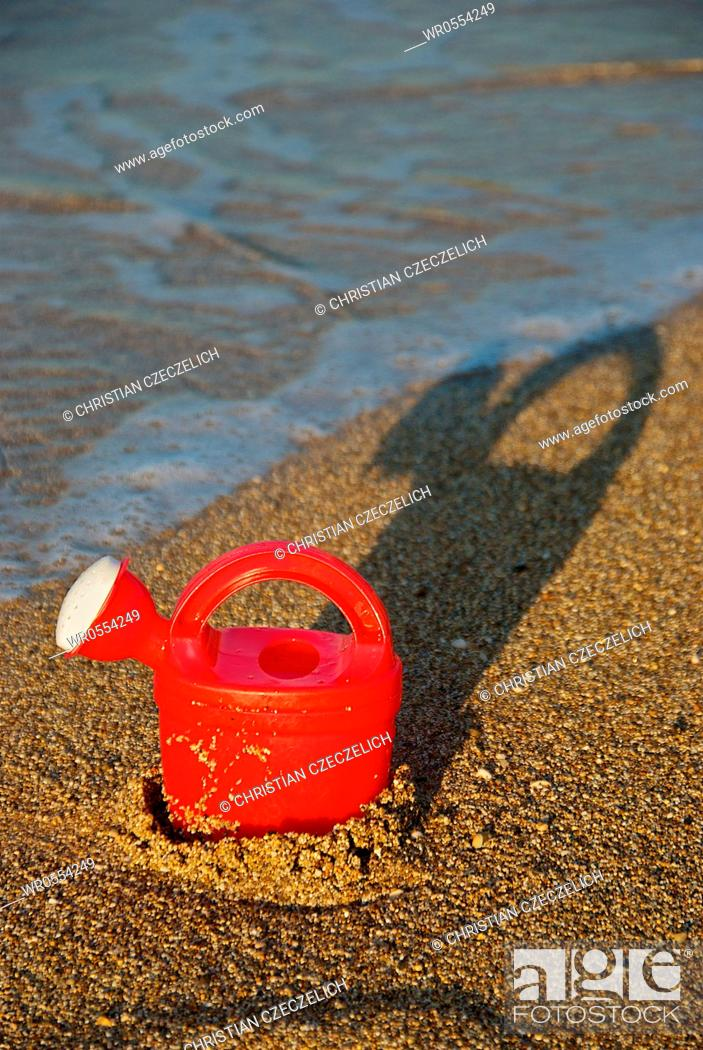 Imagen: Watering can at the beach.