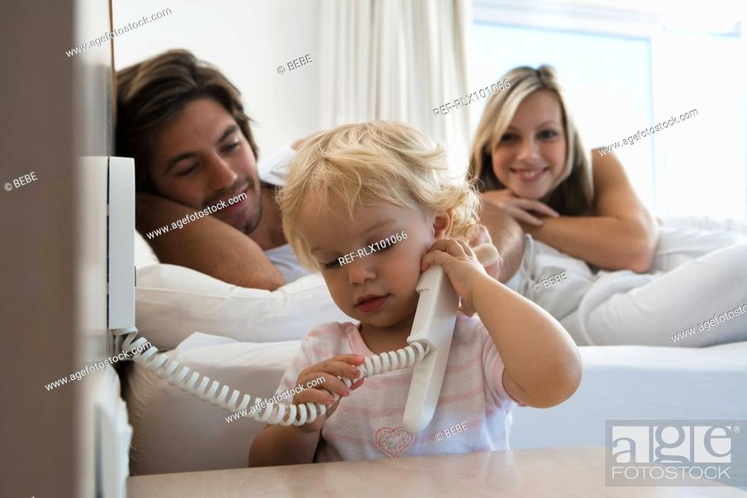 Stock Photo: Baby 12-24 months on the phone in bedroom, young parents watching.