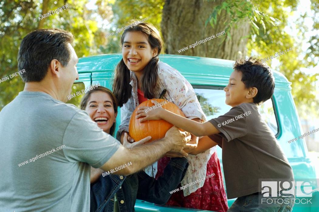 Stock Photo: Multi-ethnic family holding pumpkin.