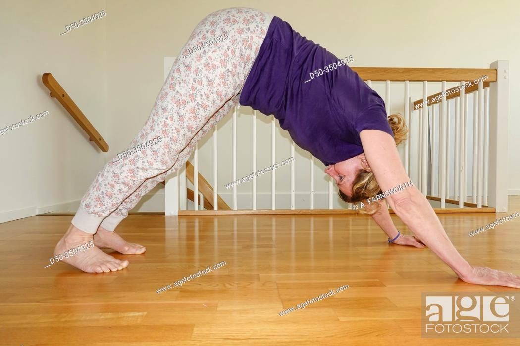 Stock Photo: A middle-aged woman does yoga at home.