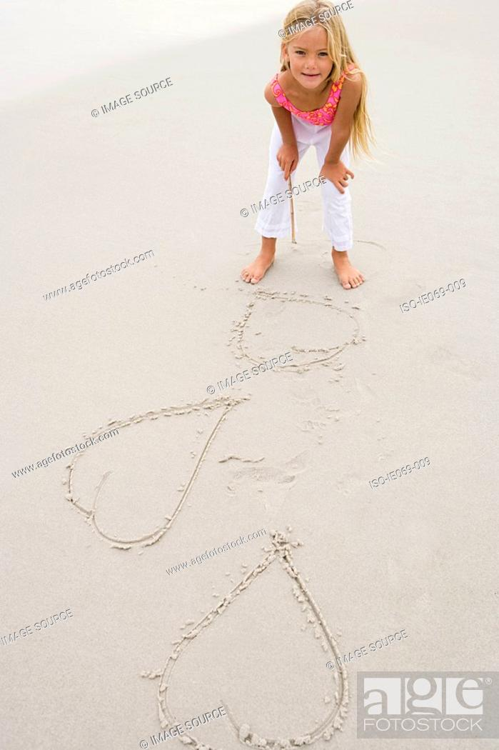 Stock Photo: Girl drawing hearts on the sand.