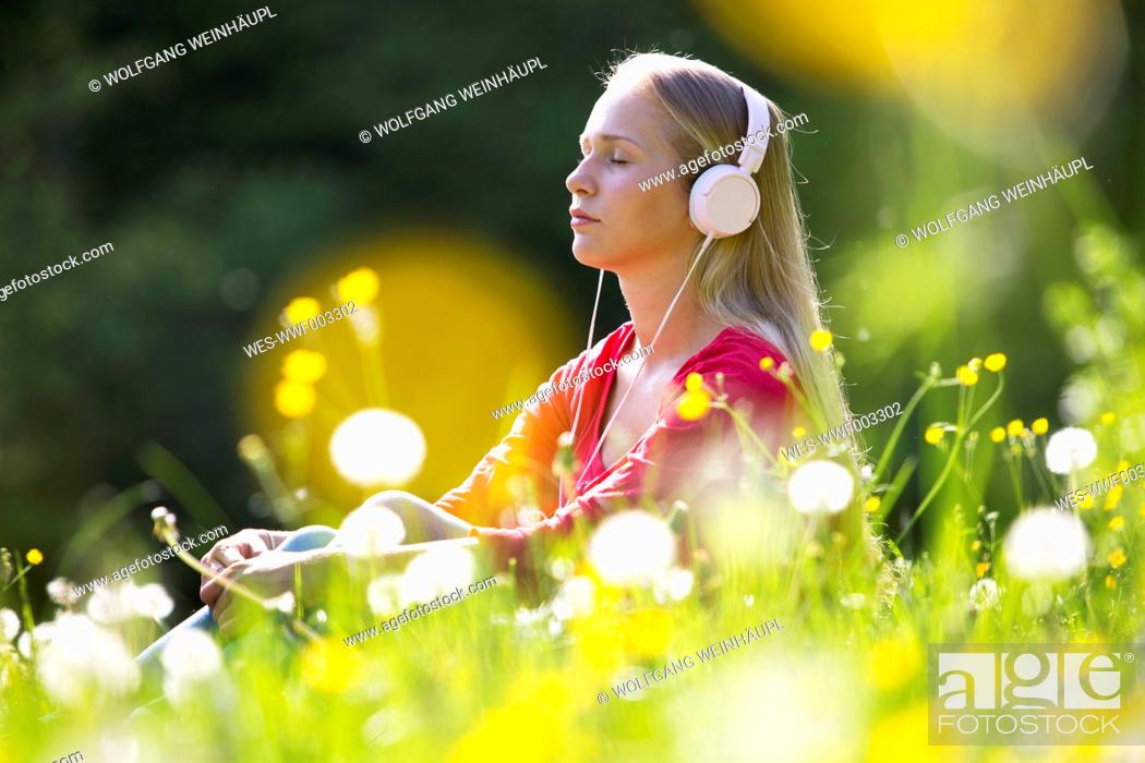 Stock Photo: Portrait of teenage girl with headphones hearing music on a flower meadow.