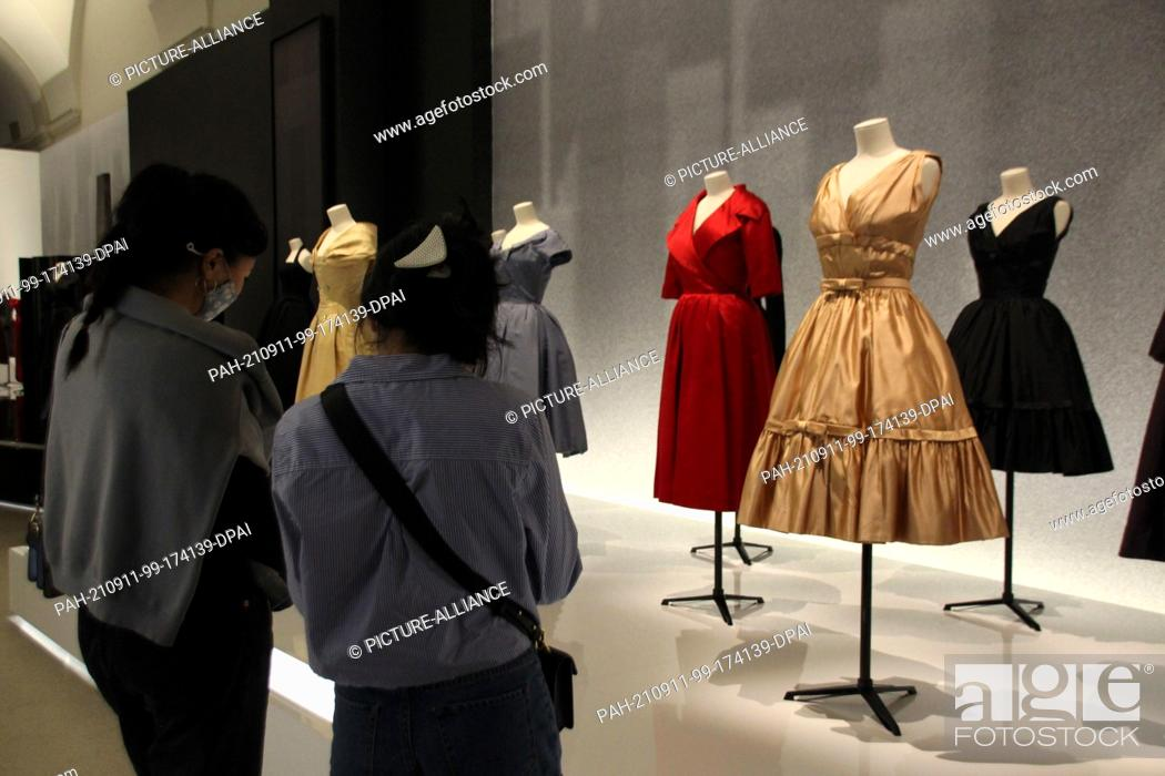 Stock Photo: 10 September 2021, US, New York: Visitors look at dresses from the exhibition honoring French fashion designer Dior at the Brooklyn Museum.
