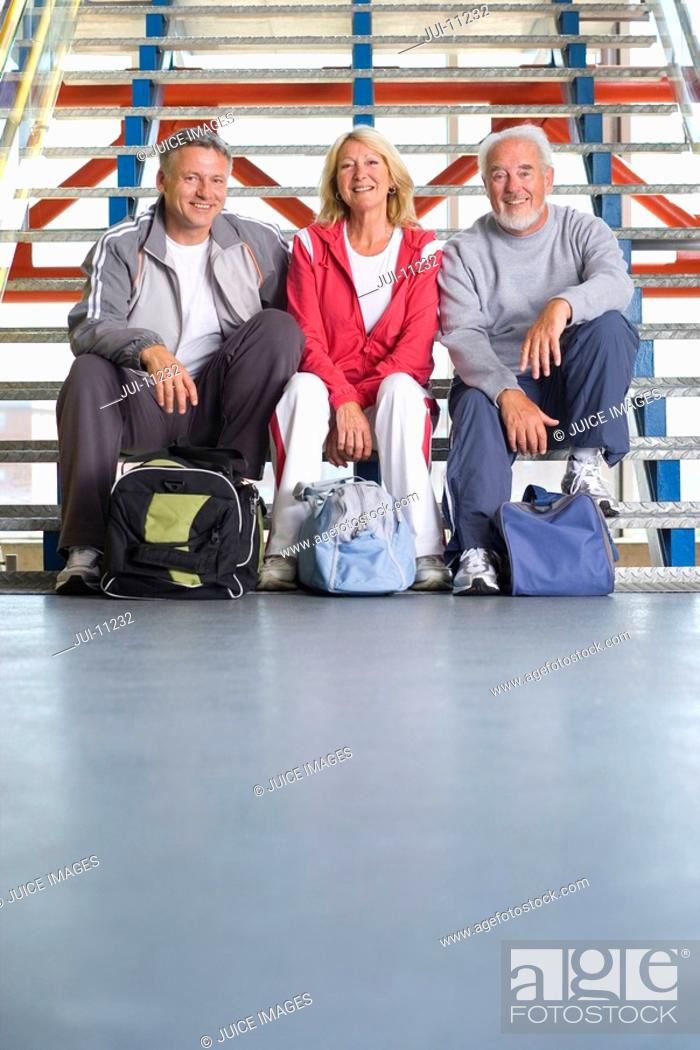 Stock Photo: Two senior men and woman with gym bags sitting on steps, smiling, portrait.