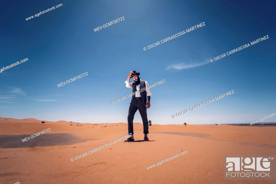 Stock Photo: Man with a beard and hat in the dunes of the desert of Morocco.