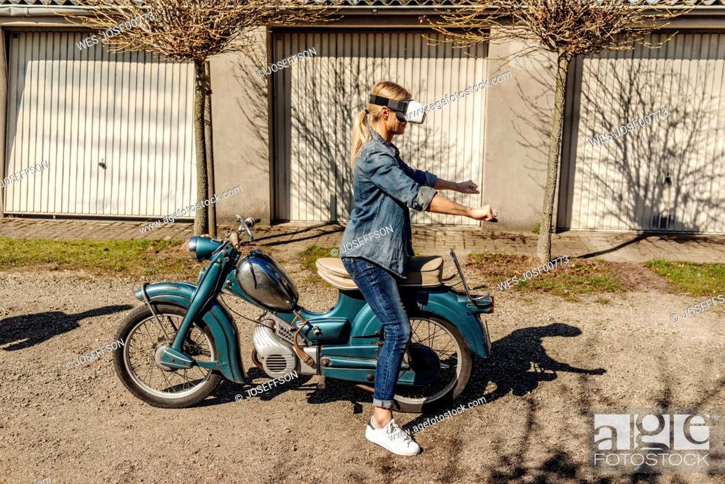 Stock Photo: Woman with vintage motorcycle wearing VR glasses.