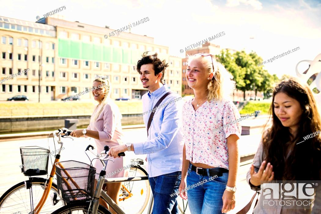 Stock Photo: Happy young friends with bicycles walking on street.