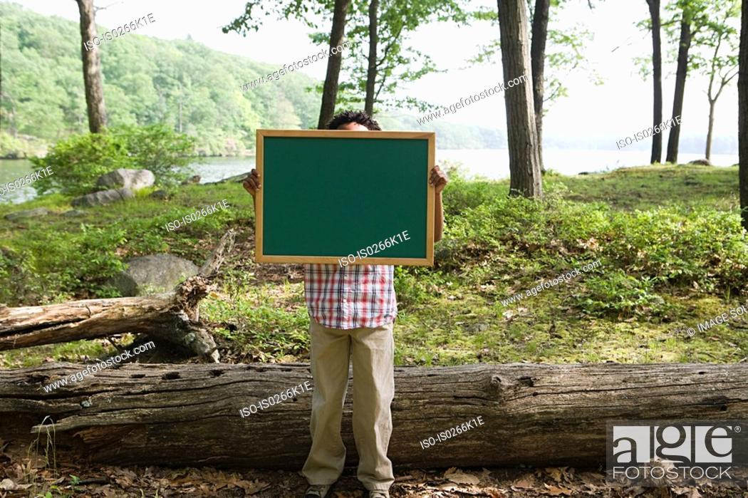 Stock Photo: A boy holding a blackboard.