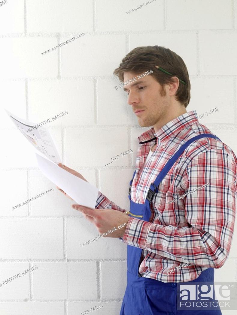 Stock Photo: Man wearing work wear is holding construction plans.