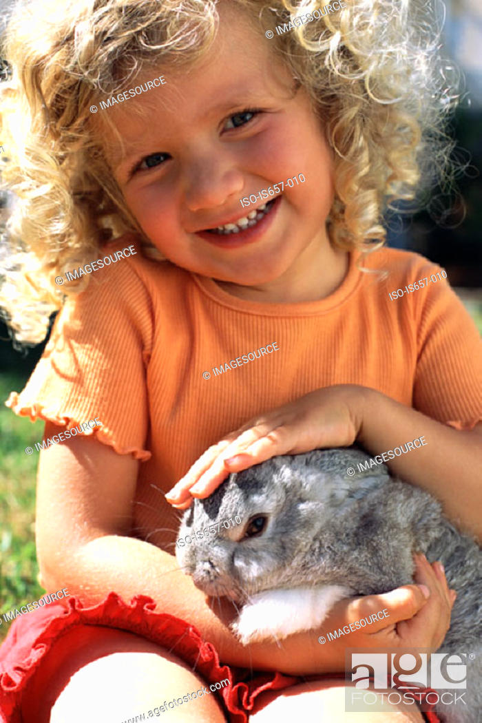 Stock Photo: Girl stroking a rabbit.