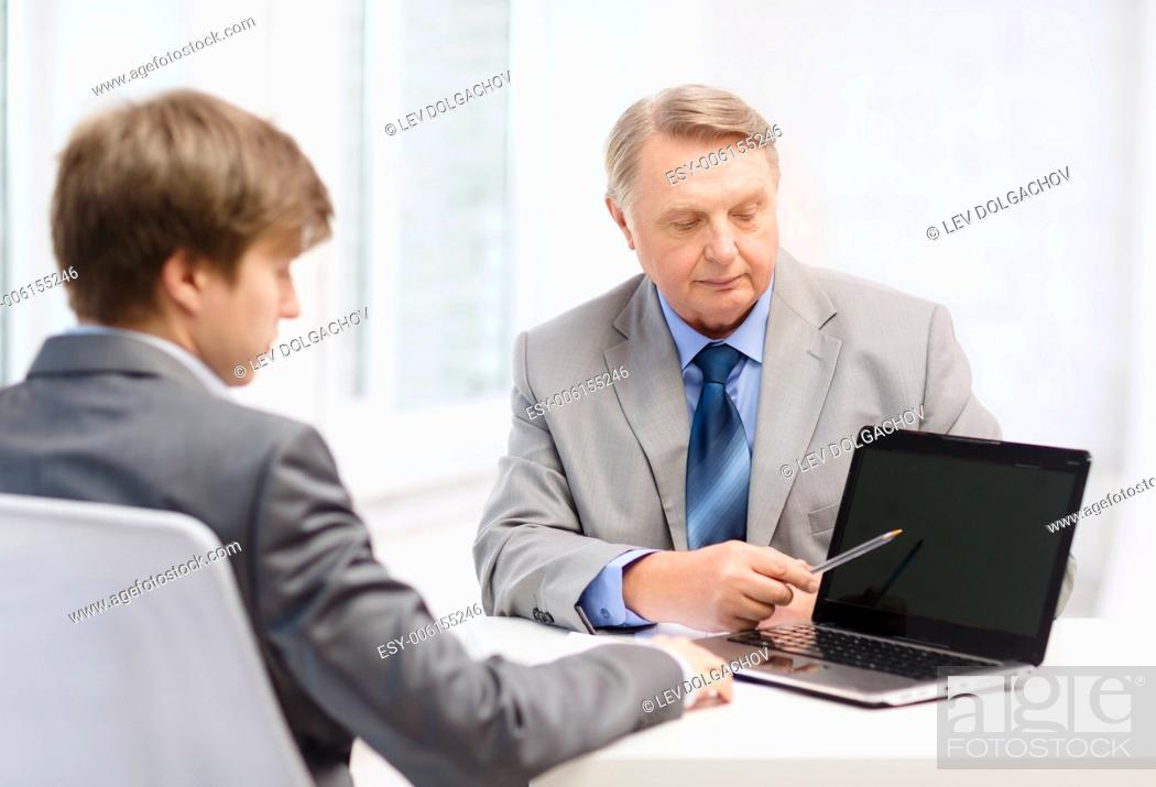 Stock Photo: business, advertisement, technology and office concept - older man and young man with laptop computer in office.
