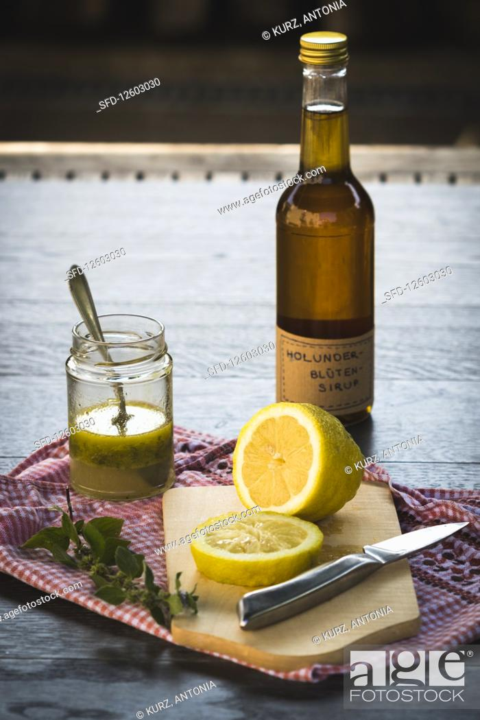 Stock Photo: A bottle of elderflower syrup behind a sliced lemon on a wooden surface.