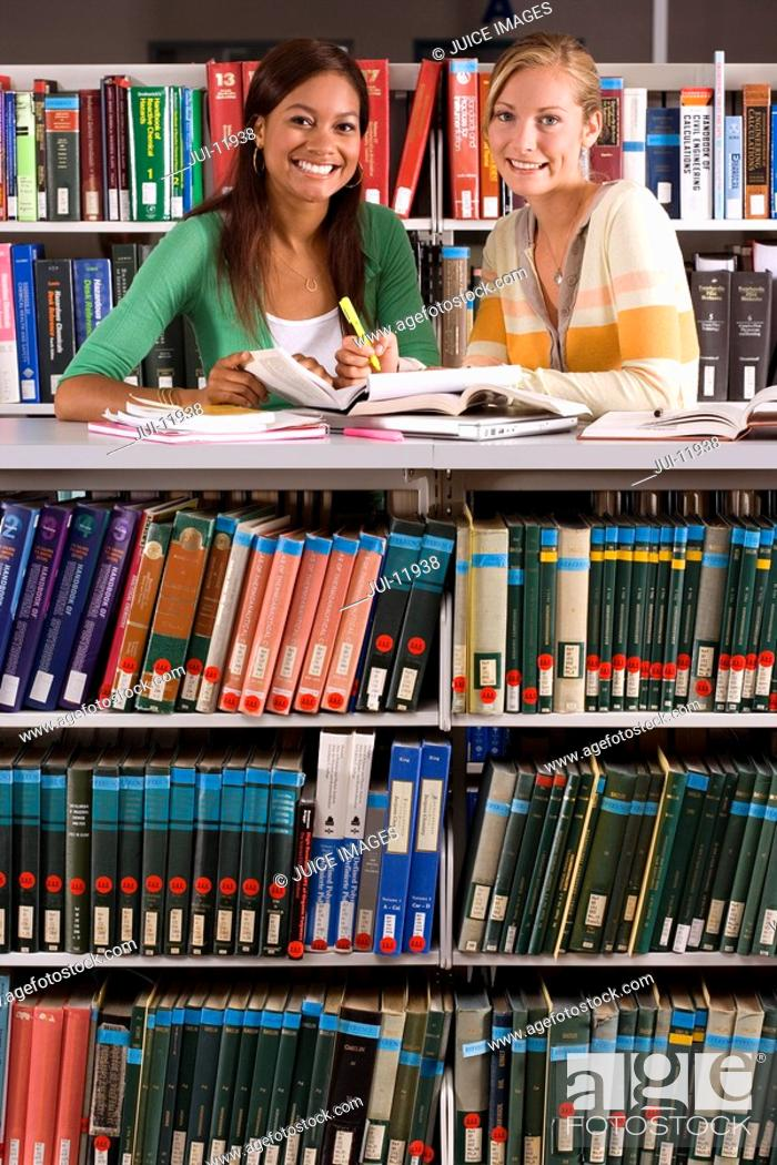 Stock Photo: Two young women studying in library, smiling, portrait.