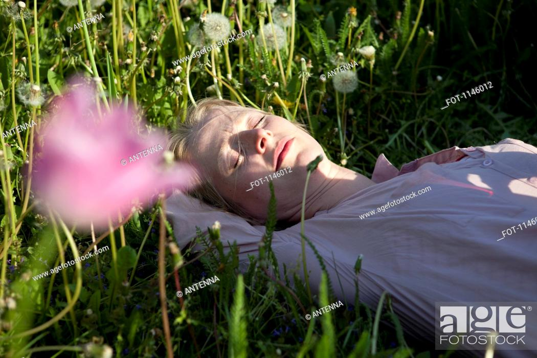 Stock Photo: A woman lying in the grass sleeping, close-up.