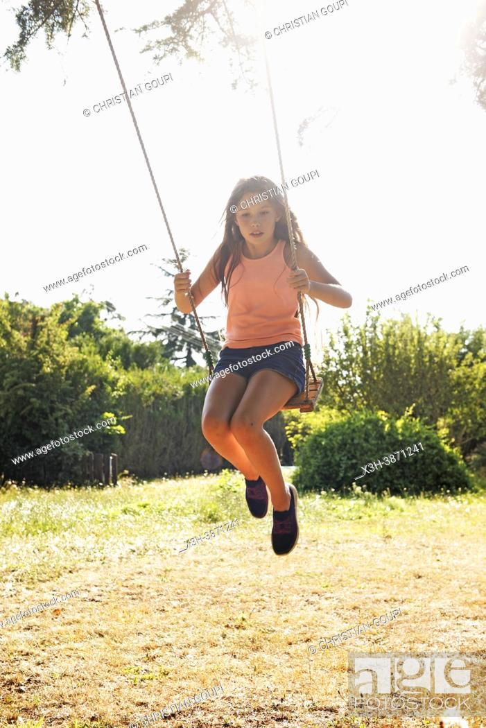 Photo de stock: Young girl in jeans shorts and pink-orange tank top on a swing in motion, France.