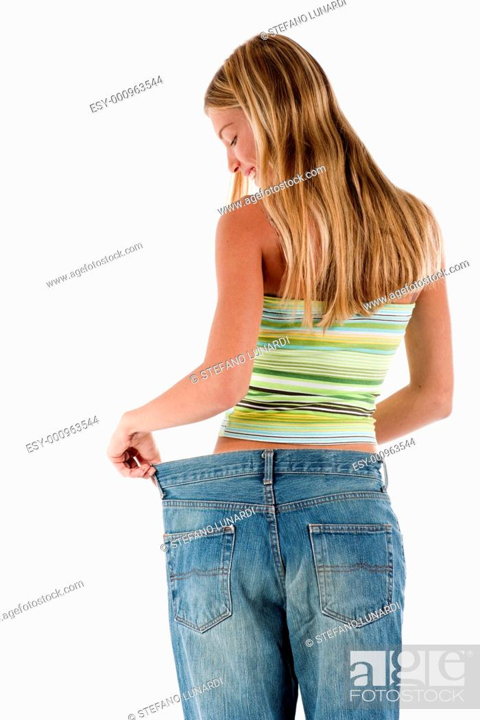 Stock Photo: Young woman became skinny and wearing old jeans.
